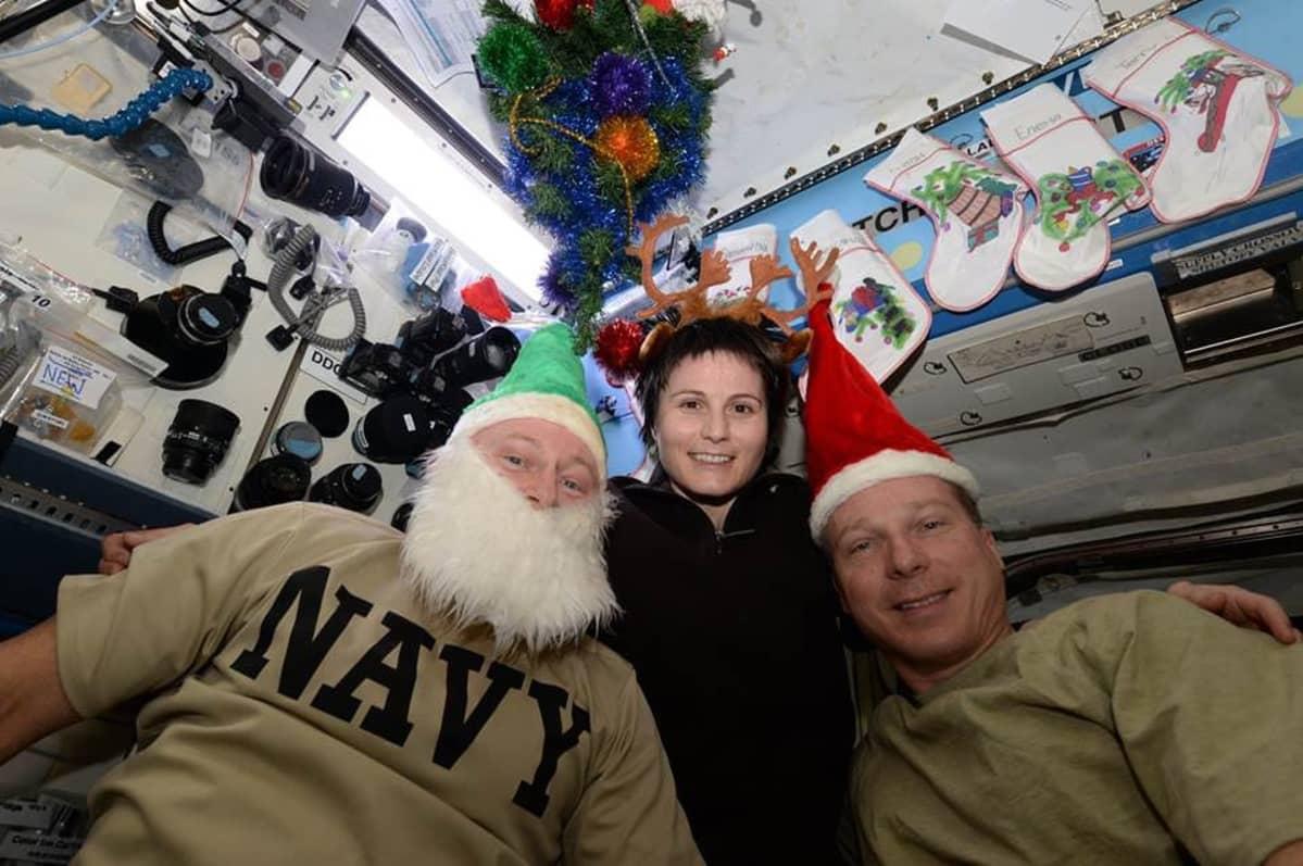 Kaksi tonttulakkipäistä miestä, joista toisella on tekoparta, ja pronsarvinen nainen. Taustalla joulusukkia seinällä ja avaruusaseman laitteistoa.
