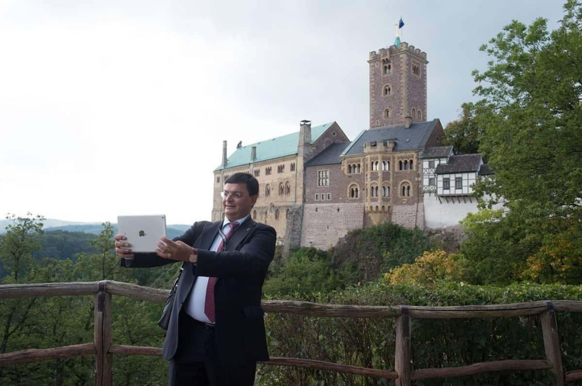 Italialainen toimittaja ottaa presidenttien tapaamisen yhteydessä selfien taustallaan Wartburgin linna.