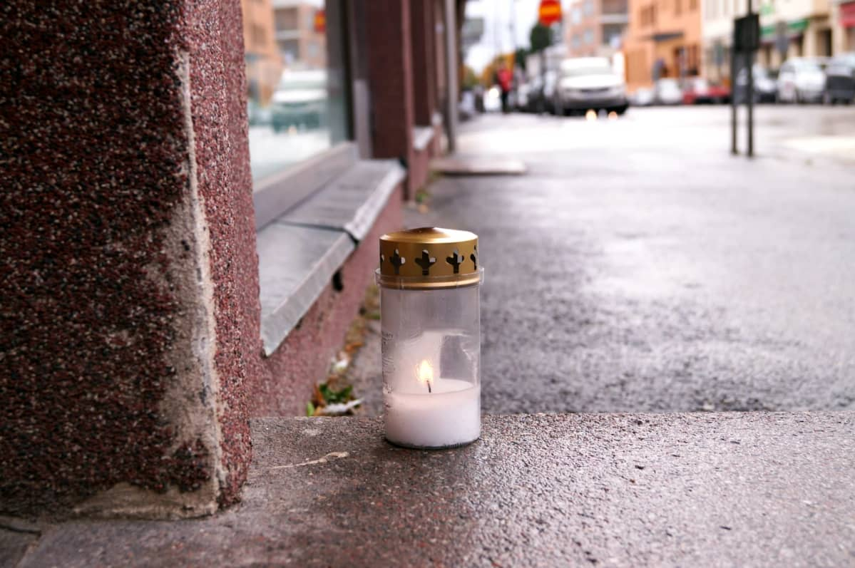 Surmapaikan edustalle jalkakäytävälle jätetty muistokynttilä.