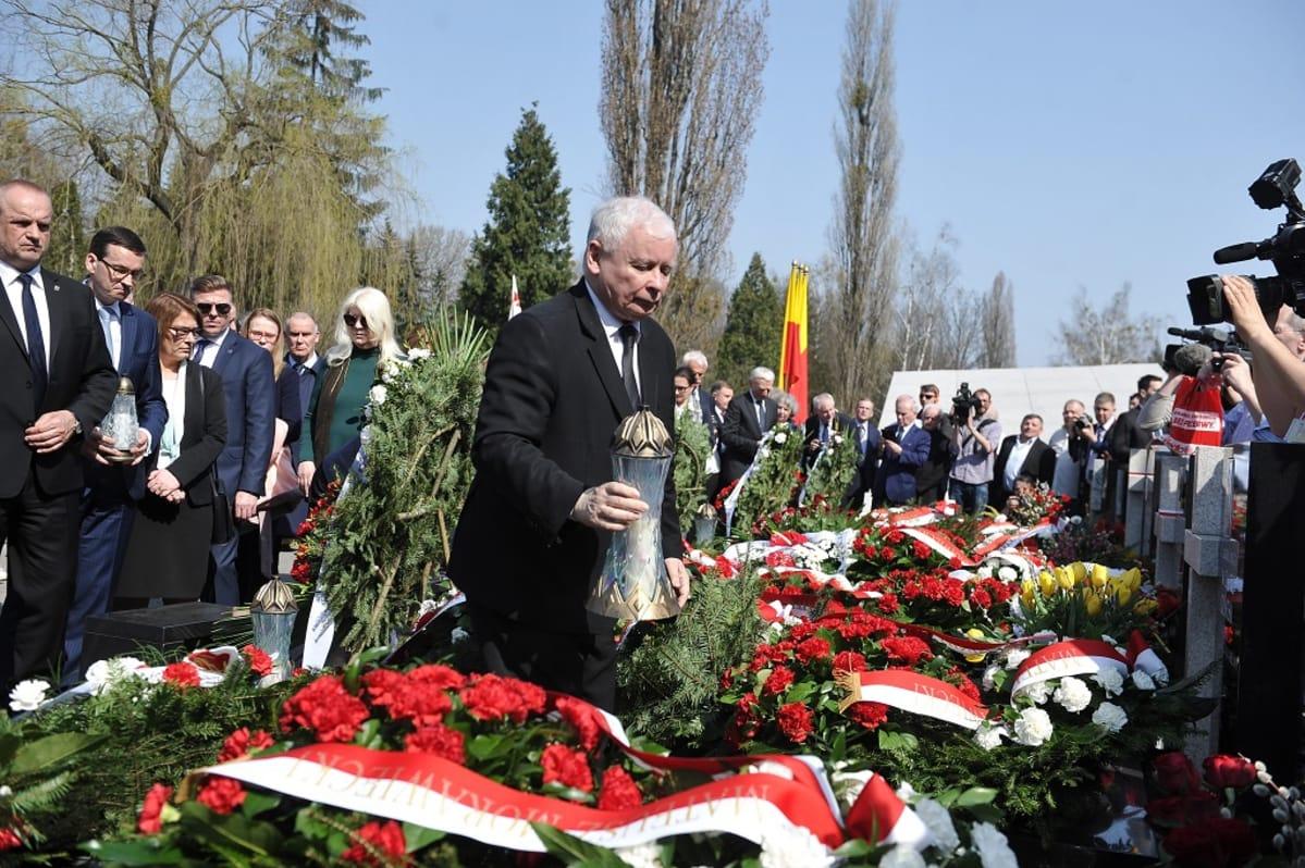 Kaczyński seisoo  seppeleiden keskellä hautausmaalla.