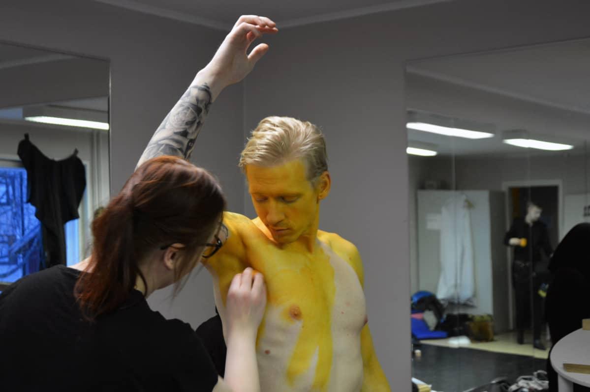 Näyttelijä Mikko Sippolaan maalataan kultamaalilla.
