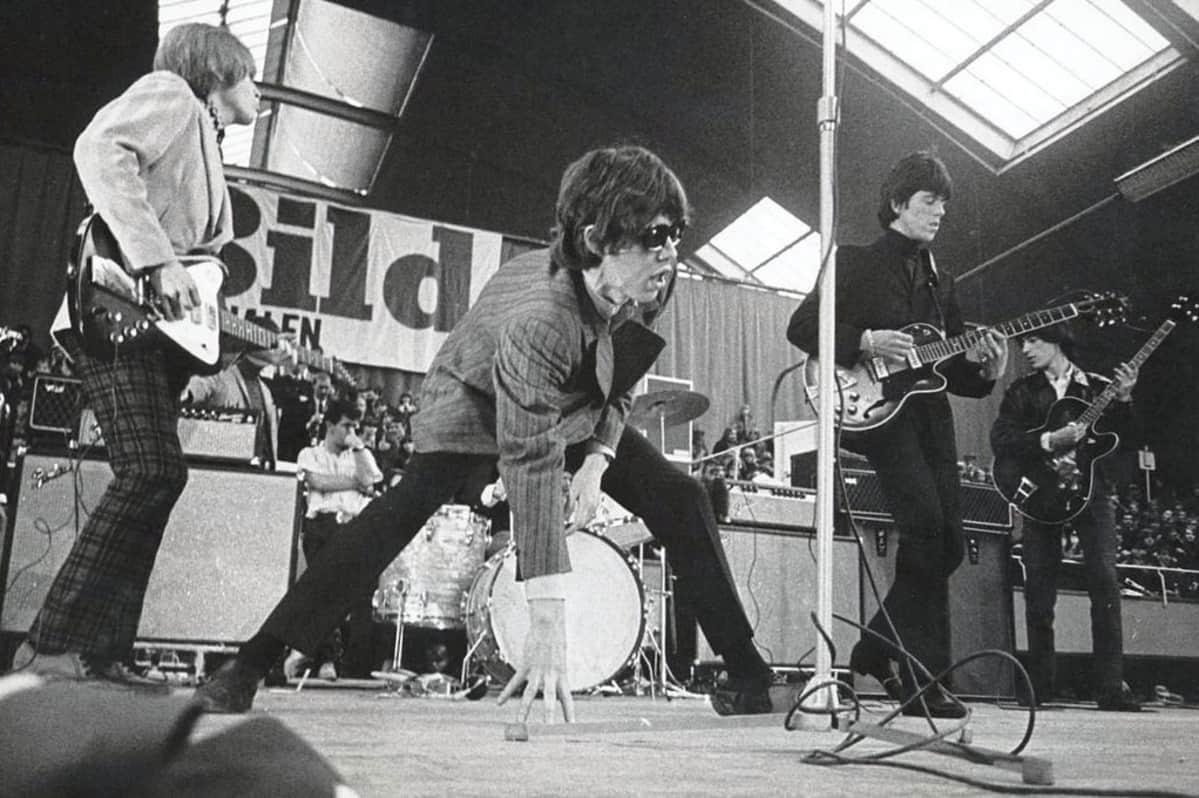 Mustavalkoinen kuva Rolling Stonesista lavalla.