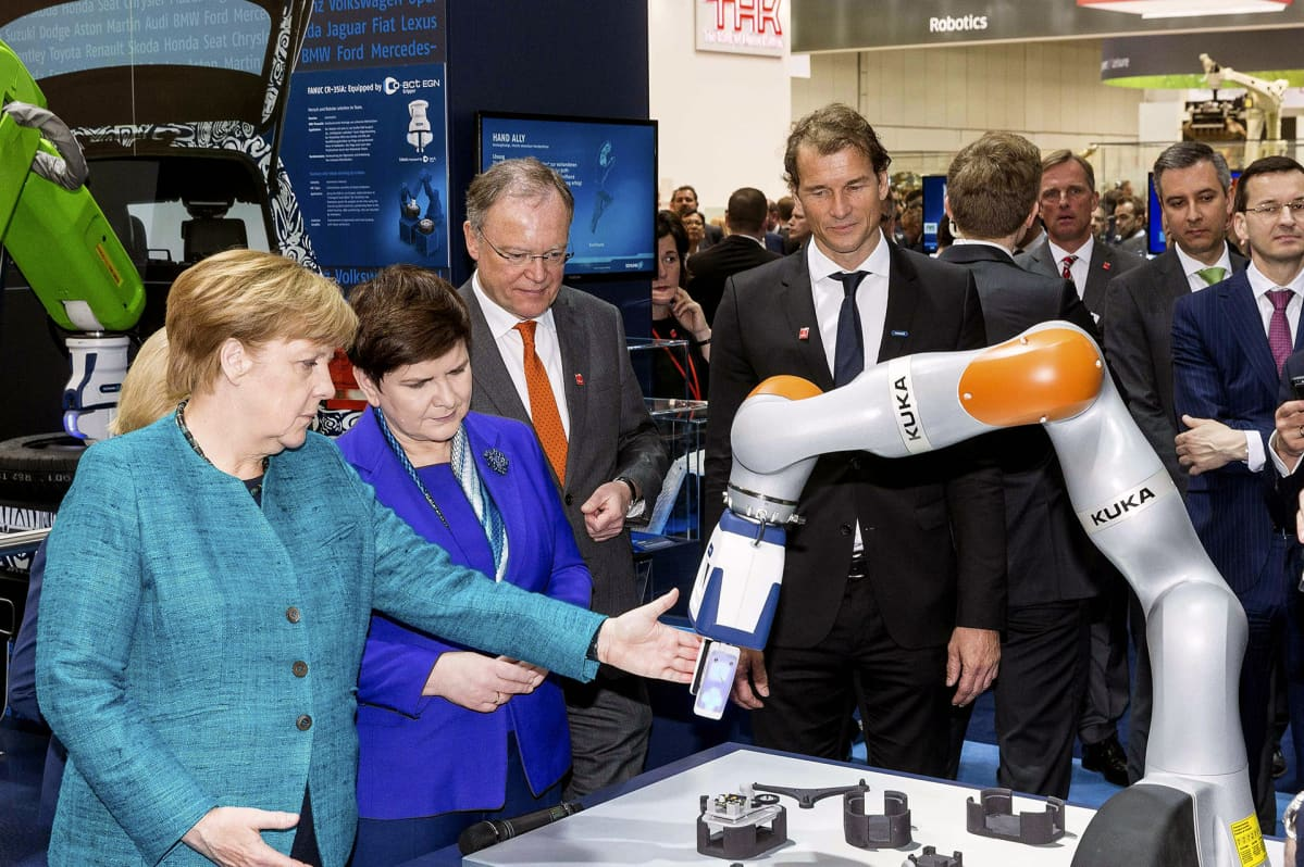 Angela Merkel ja Kuka-robotiikkaa.
