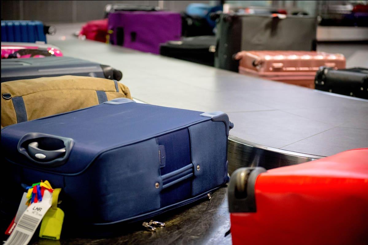 Matkalaukkuja lentokentän hihnalla.