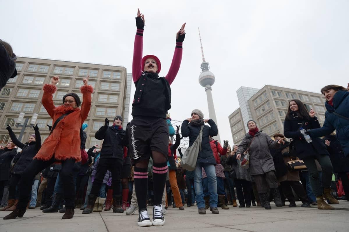 Naisia tanssimassa kadulla, takana häämöttää Berliinin televisiotorni.