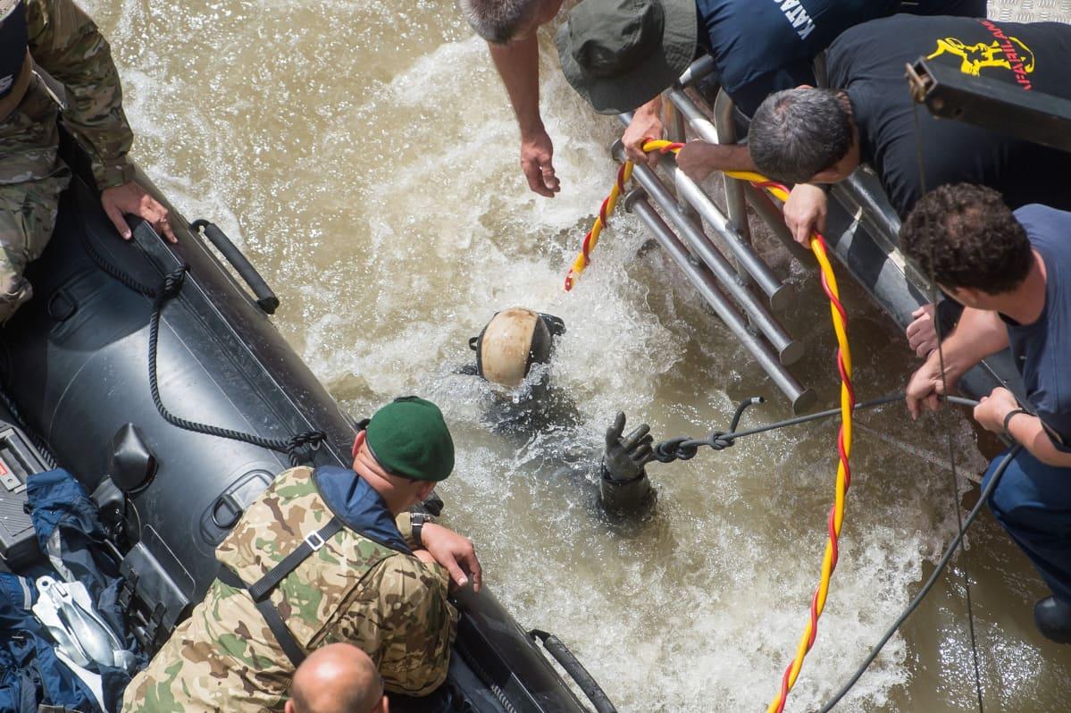Joukko pelastusmiehiä kumilautoilla. Keskellä lähes veden alla oleva sukeltaja.