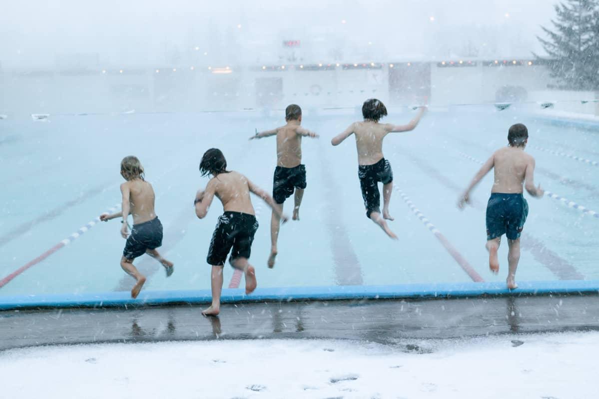 Islantilaiset pojat hyppäämässä ulkoilmauima-altaaseen.