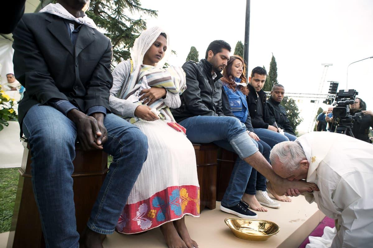 Paavi suutelee miehen jalkoja.