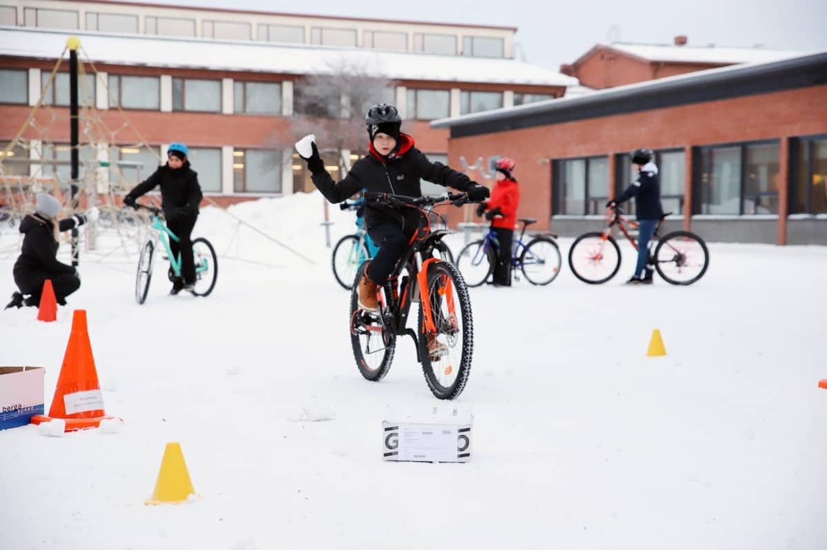 Poika ajaa pyörällä koulun pihalla ja heittää lumipalloa laatikkoon.