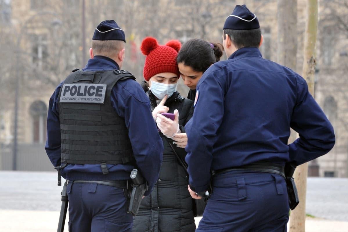 Poliisit tarkastavat papereita ulkonaliikkujilta Pariisissa.