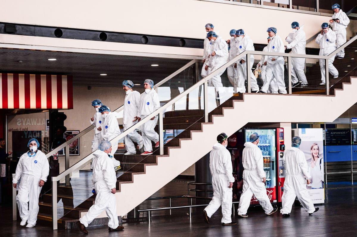 Terveydenhuoltohenkilökunta pukeutunut suojavarusteisiin Moskovan  Sheremetyevon lentokentällä 18. maaliskuuta.