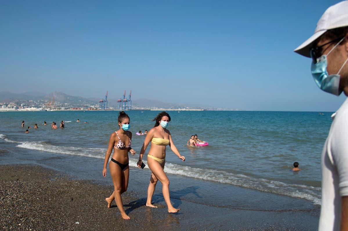 Kasvomaskeihin pukeutuneita ihmisä uimarannalla Malagassa.