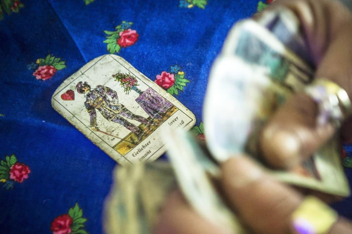 Tarot-kortteja korteista ennustajan kädessä.