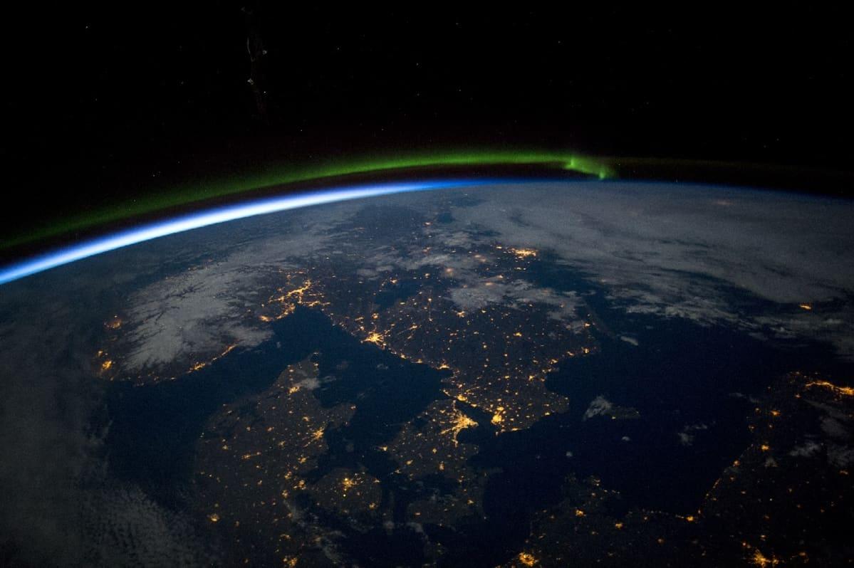 Maapallon kaareva pinta, jolla kaupungit näkyvät valokeskittyminä.