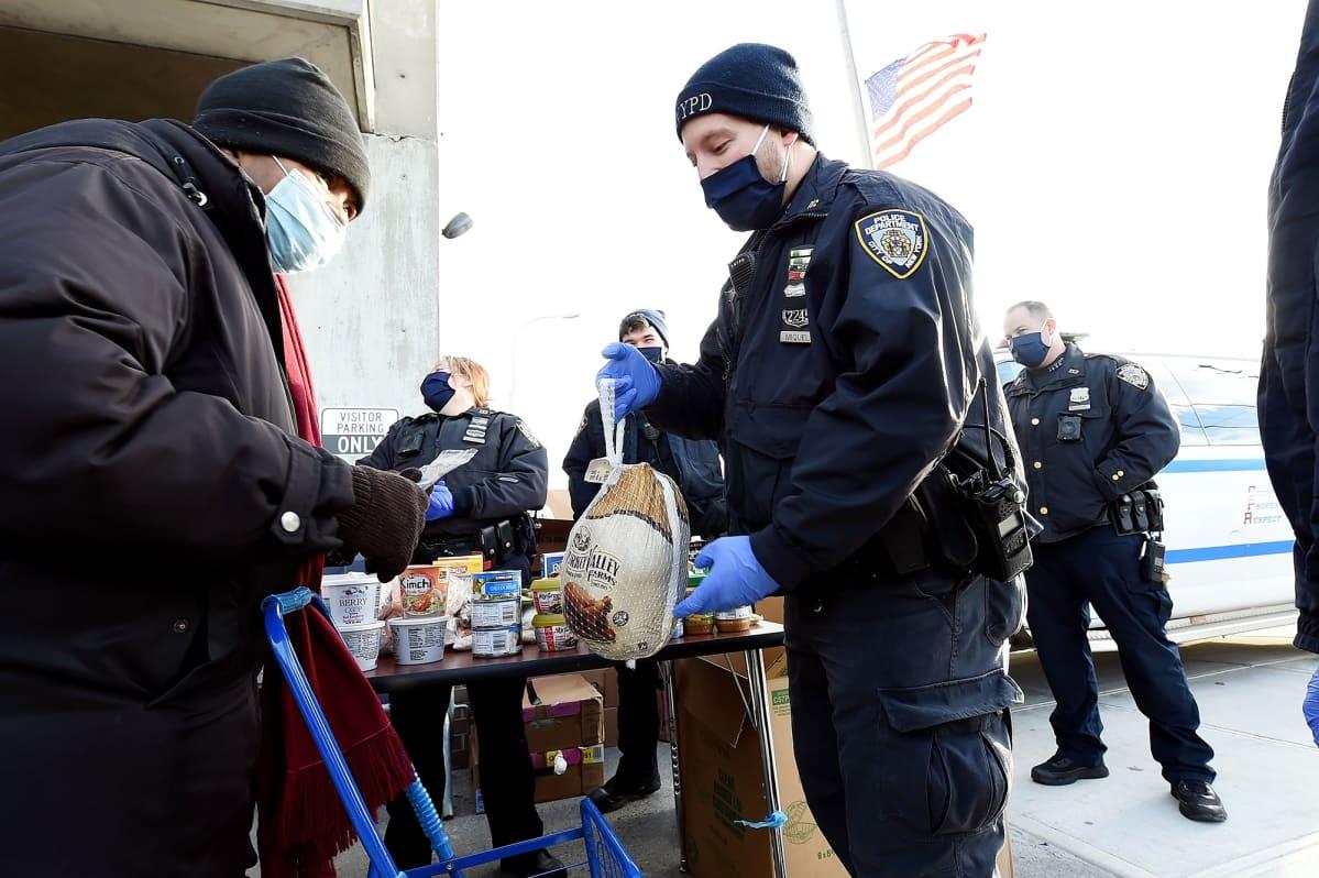 Poliisi antaa kalkkunan henkilölle hyväntekeväisyystilaisuudessa New Yorkissa.