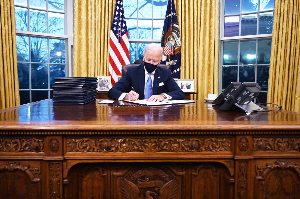 Joe Biden allekirjoittaa papereita Valkoisessa talossa.
