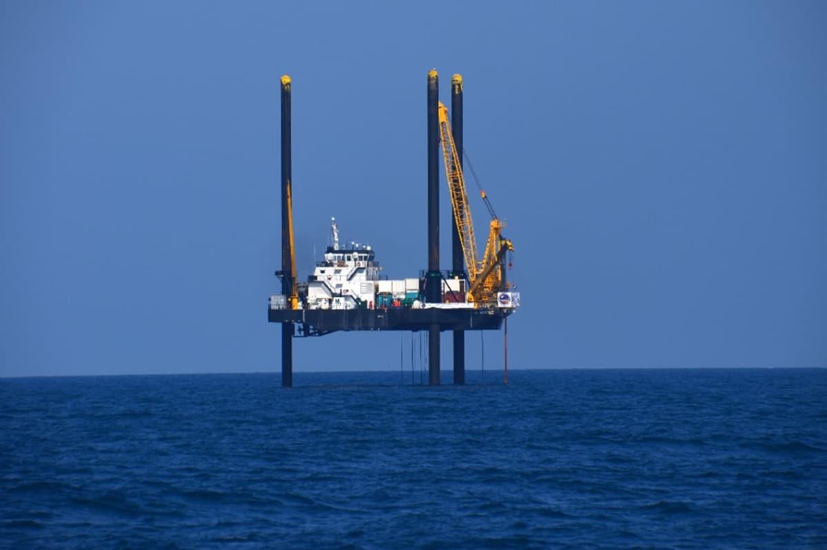 Kolmen tolpan varassa merenpinnan yllä oleva alus nostokurkineen.