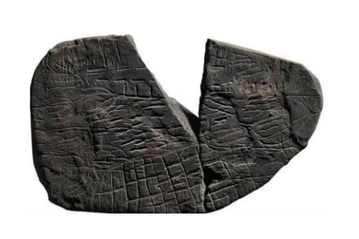 Uurteiden peittämä kivi, josta puttuu kiilan muotinen kappale.