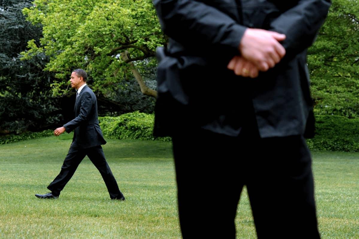 Yhdysvaltain presidentti Barack Obama kävelee Valkoisen talon nurmikolla Salaisen palvelun miehen tarkkaillessa ympäristöä.
