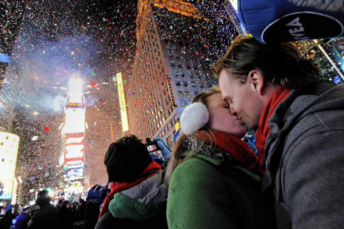 Pari suutelee kadulla, taustalla uudenvuodenjuhlintaa.