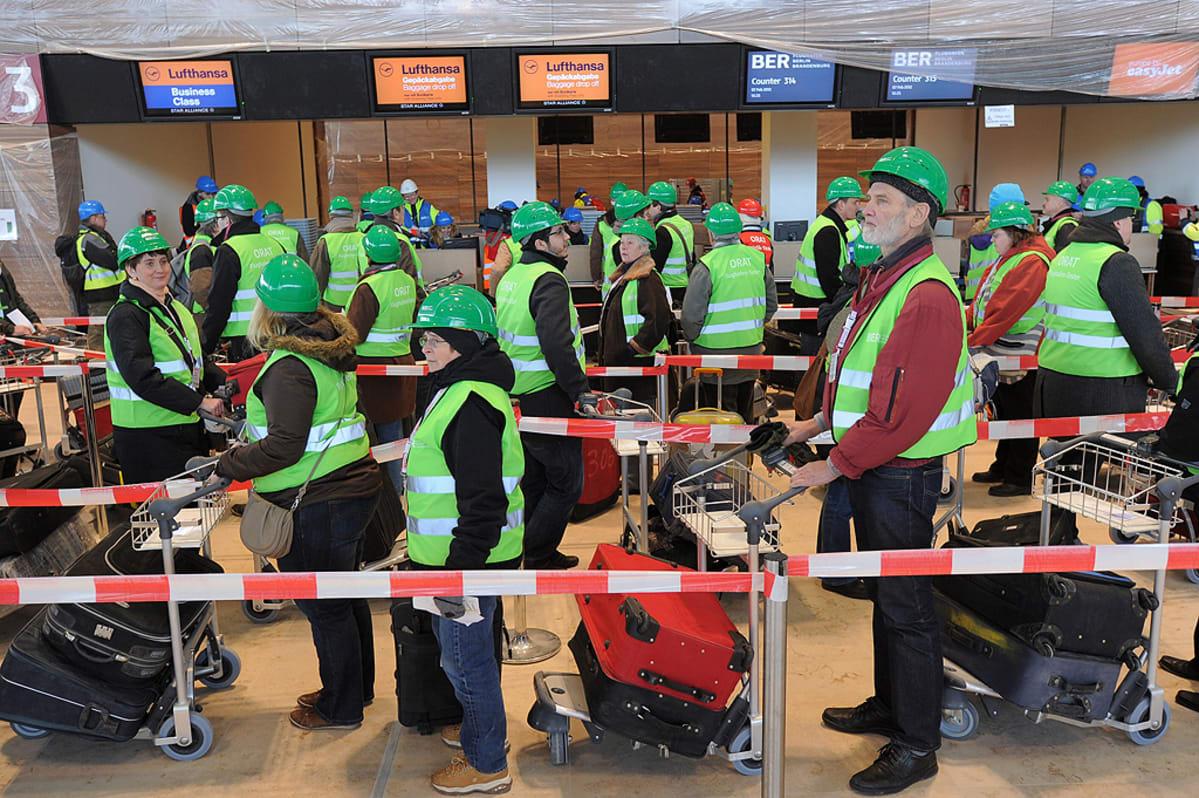 """Vapaaehtoiset jonottavat check in -tiskeille Berlin-Brandenburgin lentoaseman """"koeajon"""" aikana."""