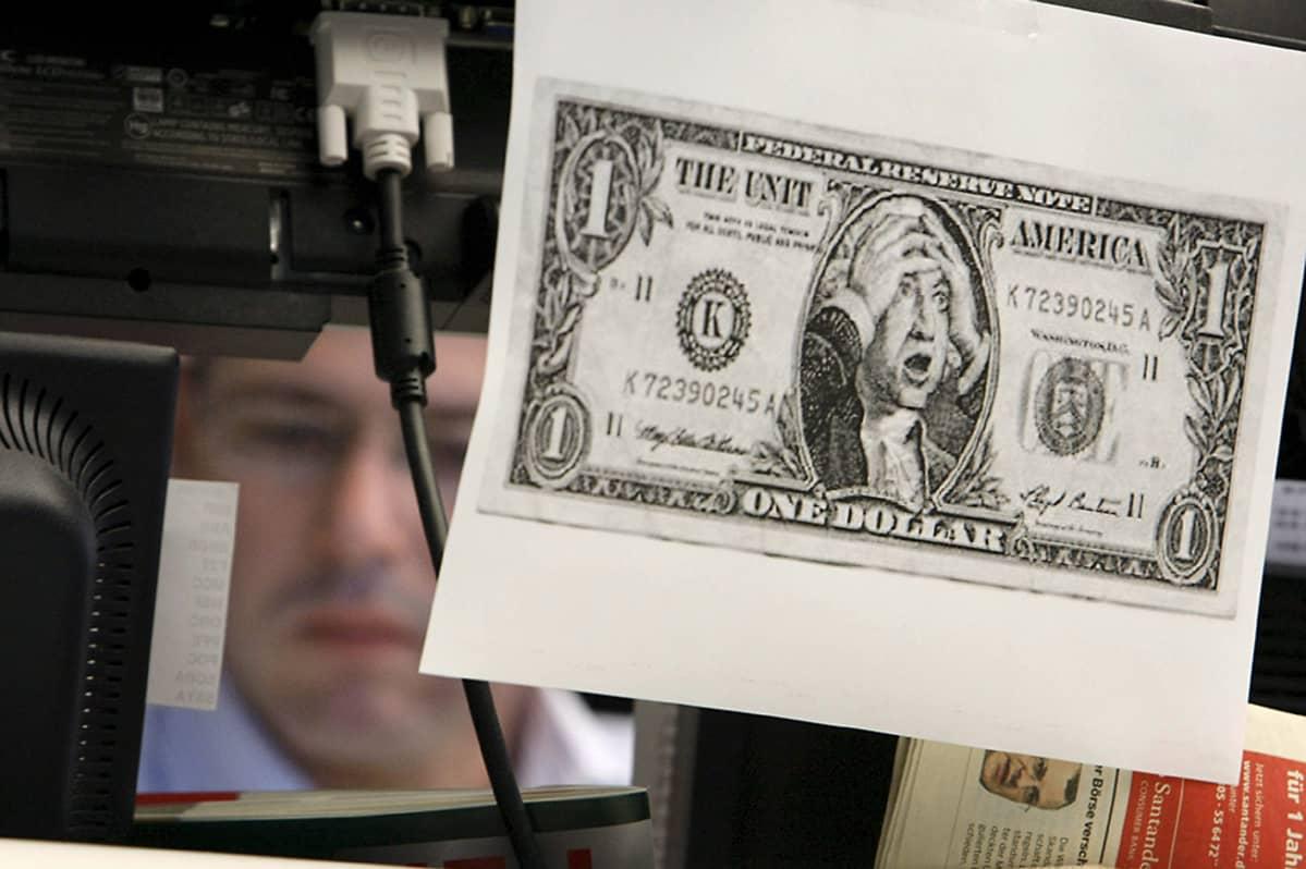 Pörssimeklarin työpisteen etupuolelle on tulostettu Yhdysvaltain valedollari valkoisella pohjalla.