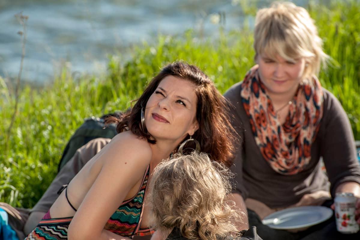 Kolme naista piknikillä ruohikossa