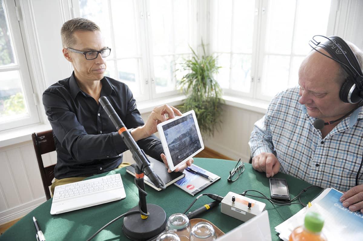 Pääministeri Alexander Stubb esittelee aamulla ottamiaan maisemakuvia ohjelman vetäjälle Jari Niemelälle.