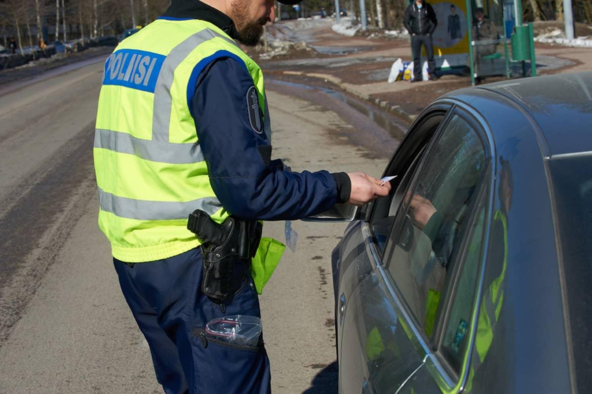 Poliisi tarkistamassa ajokorttia