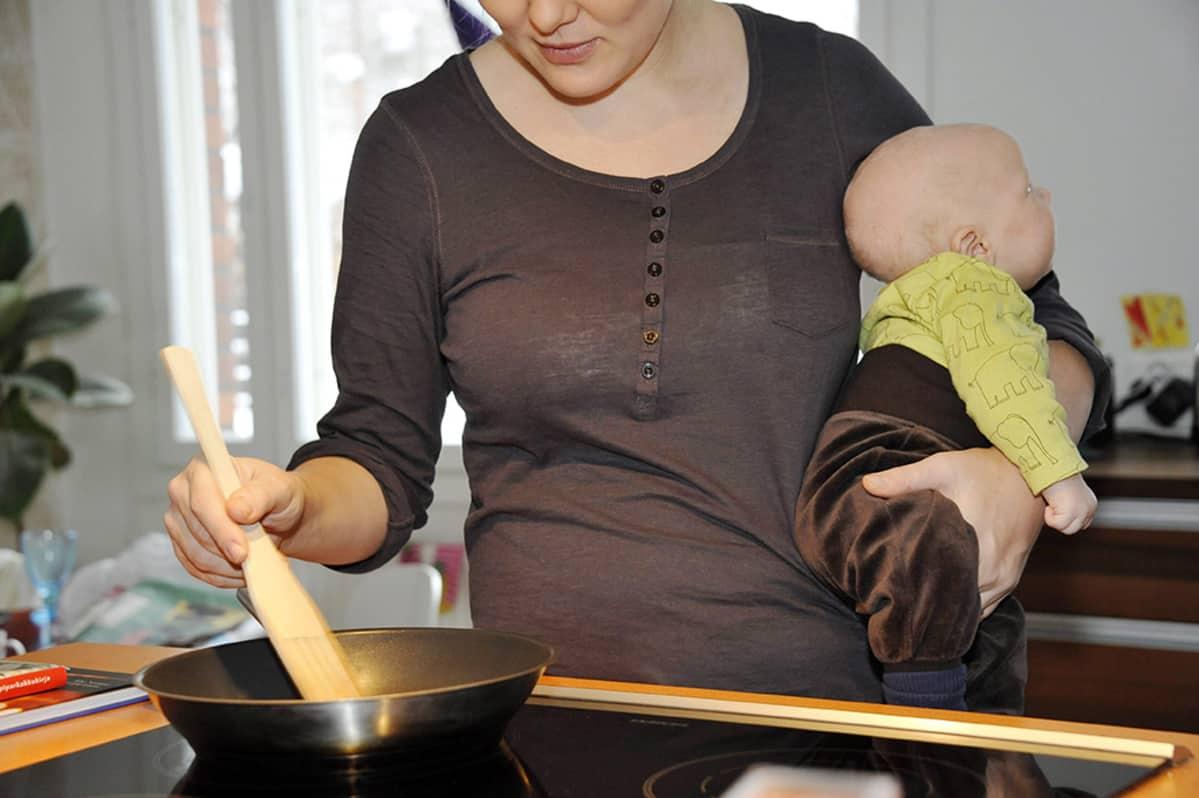 Äiti laitta ruokaa - vauva kainalossa.