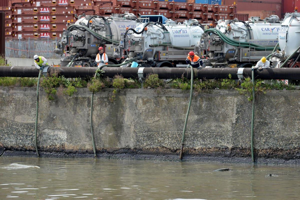 Työntekijät koettavat imeä öljyä pois Polcevera-joesta Genovassa 23.4. 2016.
