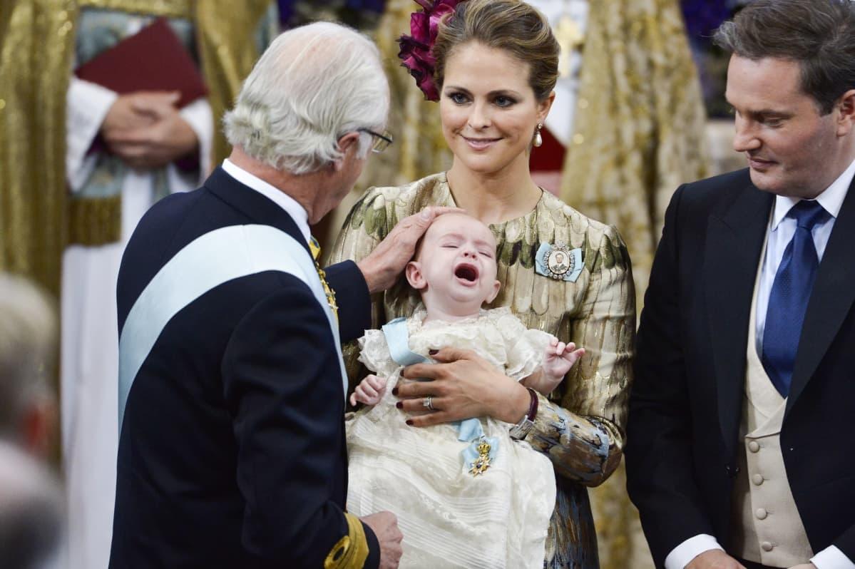 Kaarle Kustaa silittää kolmannen lapsenlapsensa prinssi Nicolasin päätä kastetilaisuudessa.