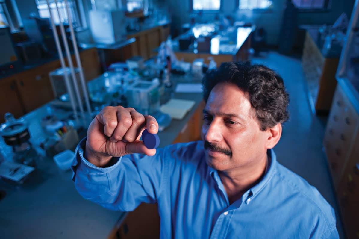 Kemisti Mas Subramanian pitää käsissään sinistä tablettia laboratoriossa.