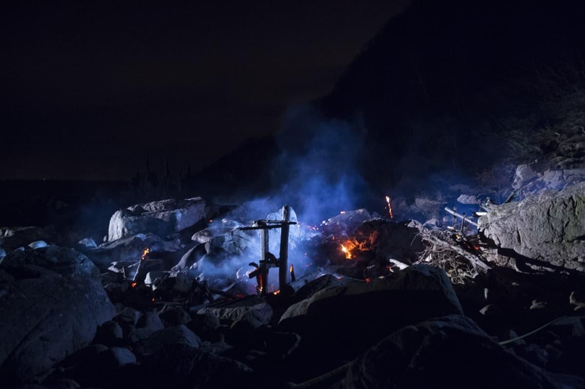 Puutornin hiiltyneet jäännökset yöllä kuvattuna.