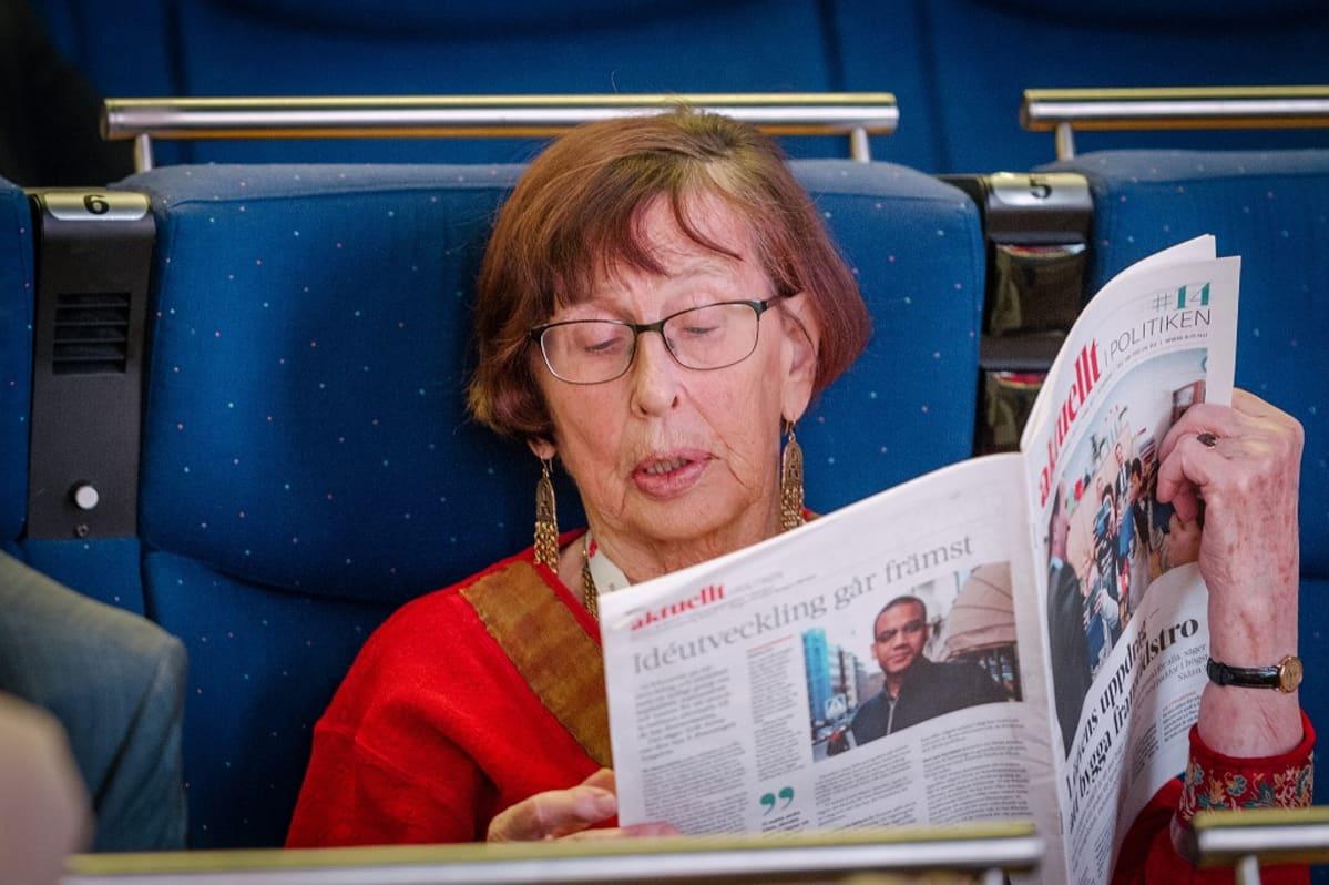 Birgitta Dahl lukemassa sanomalehteä.