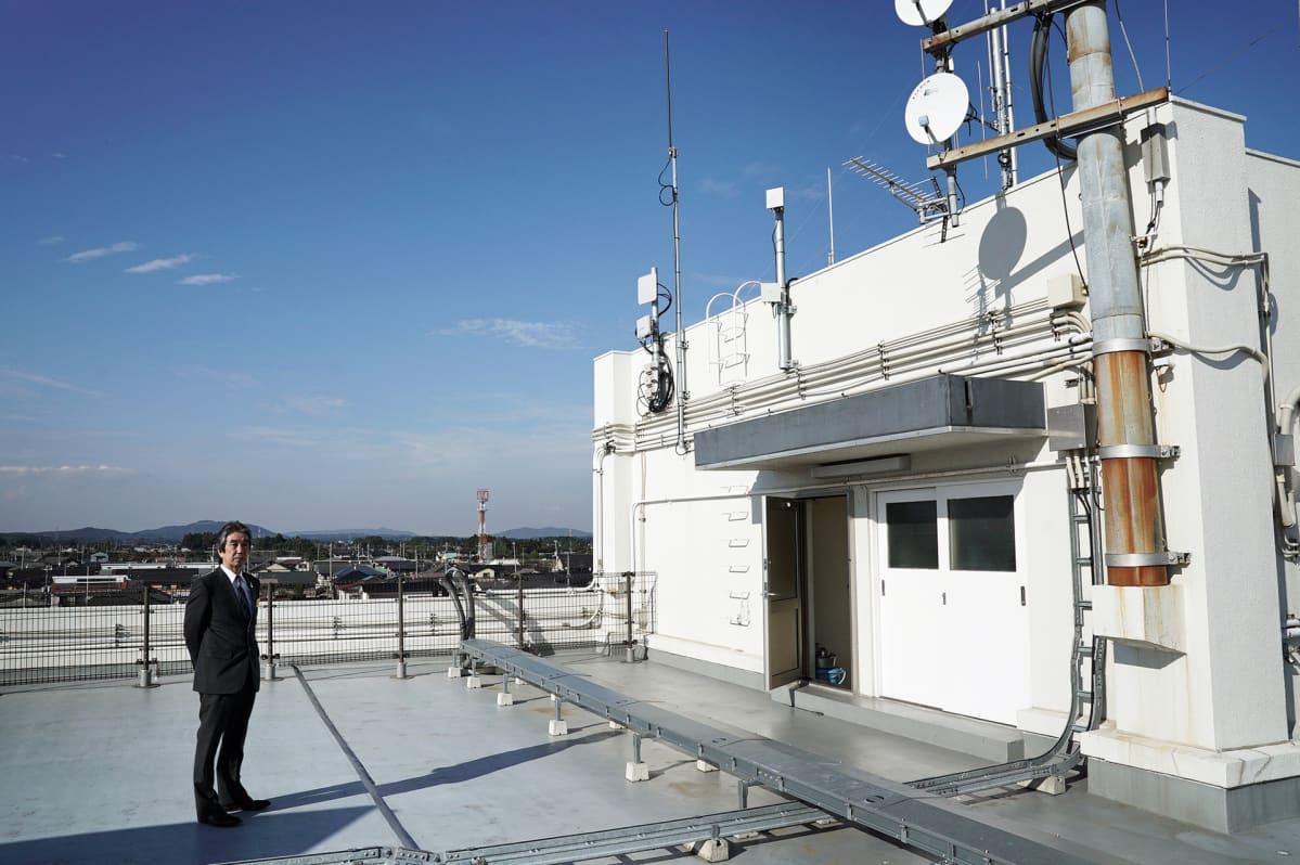 Kaupunginjohtaja Morio Furuyama valkoisen rakennuksen katolla. Rakennuksessa on lautasantenneja ja muuta hälytysjärjestelmään kuuluvaa.