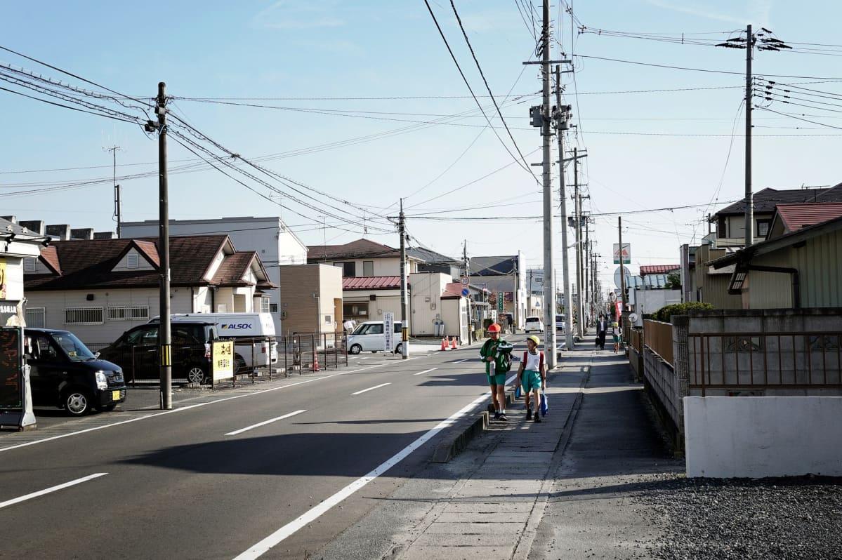 Yleiskuva Higashimatsushiman kaupungista, jossa on matalia taloja ja sähköpylväiden päässä kulkevia johtoja.