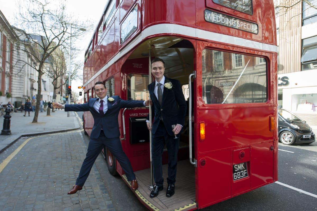 Miehet seisovat punaisen bussin takaosassa Lontoossa maaliskuussa 2014. He solmivat avioliiton ensimmäisten joukossa, kun samaa sukupuolta olevien avioliiton salliva laki astui voimaan.