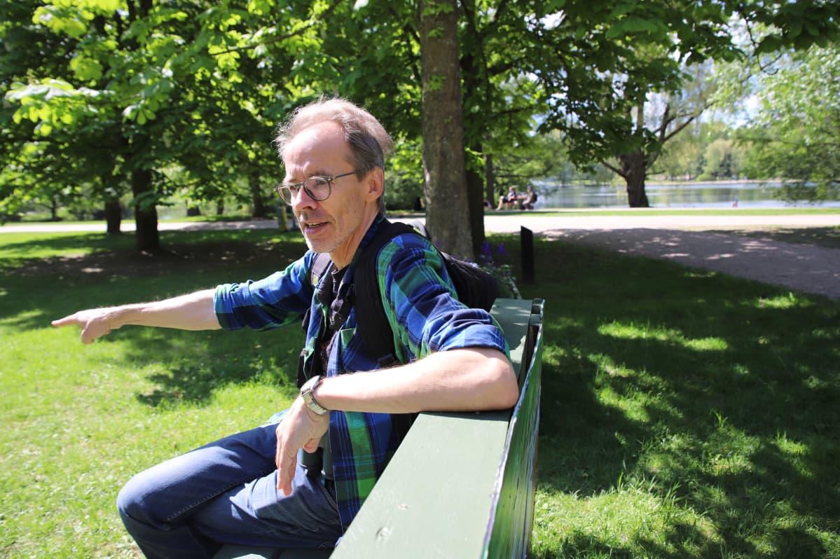Kaupunkiekosysteemitutkimuksen professori Heikki Setälä istuu Pikku-Veskun puistossa