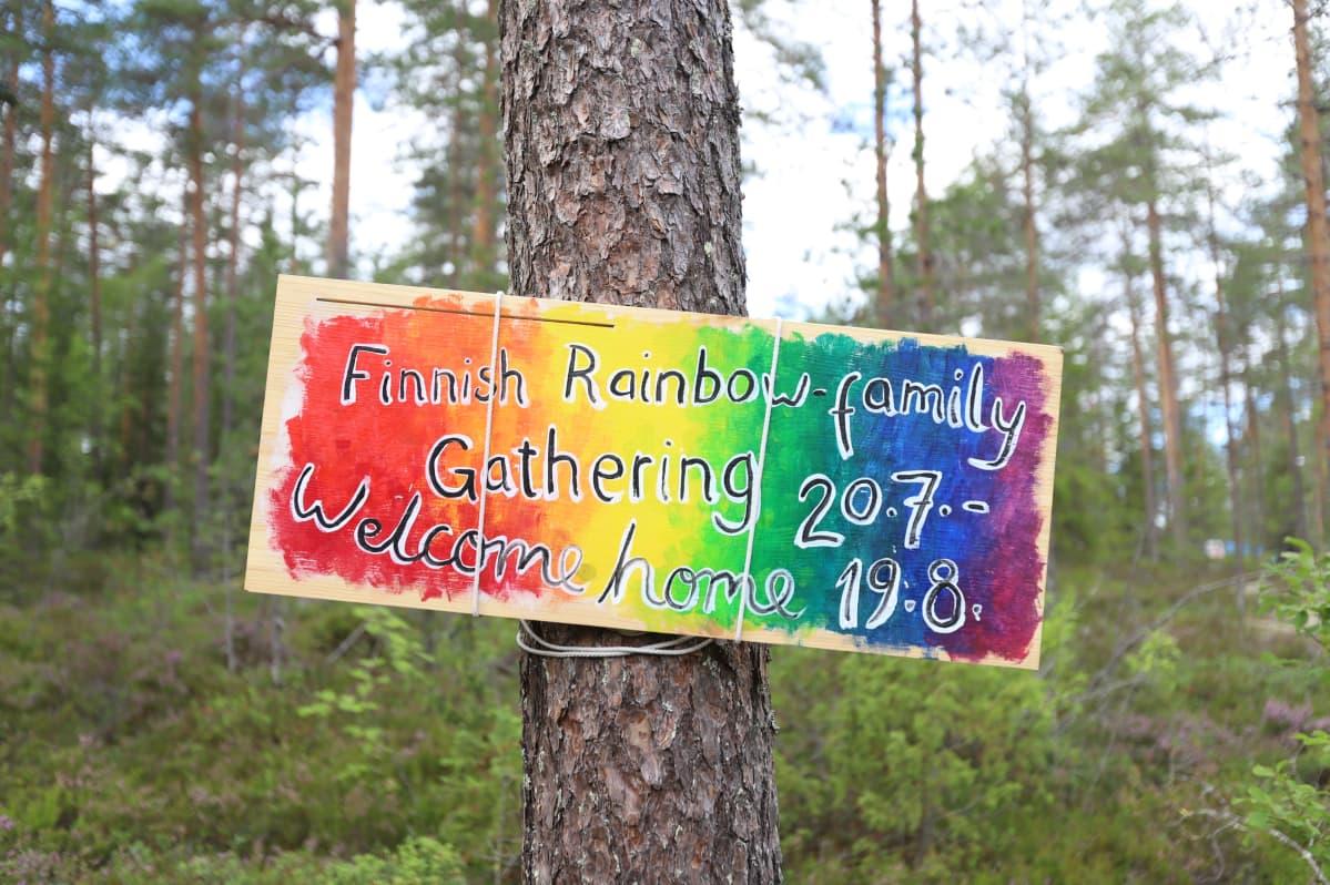 Puussa roikkuu kyltti, joka toivottaa Rainbow-perheen tervetulleeksi leirille