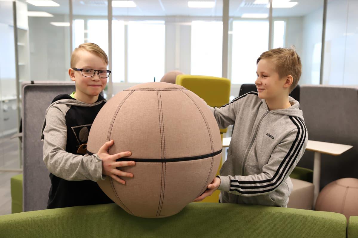 Nico Varis ja Eetu Kinnunen nostavat pallojakkaraa avoimessa opiskelutilassa.