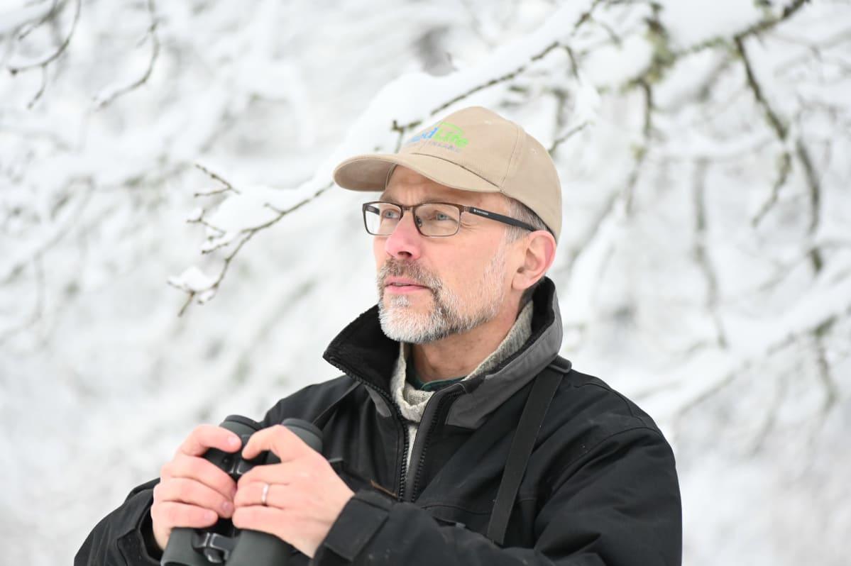 Lintuharrastaja kiikarin kanssa talvisessa luonnossa.