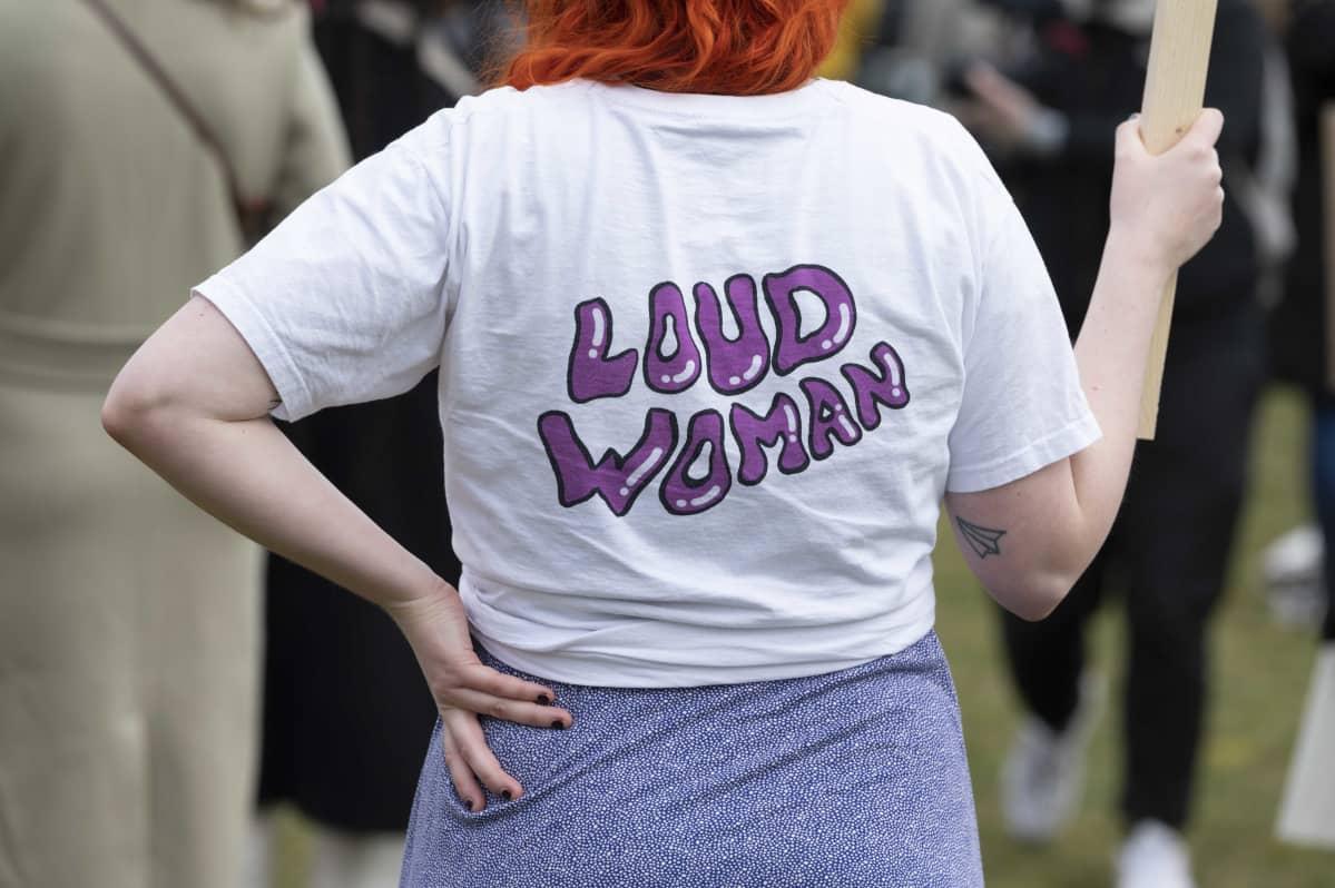 Nainen on pukeutunut paitaan, jossa lukee Loud woman.