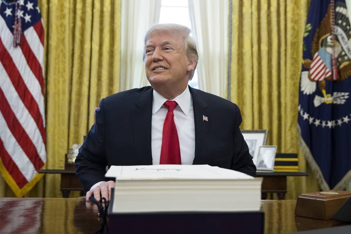 Trump työpöytänsä takana.