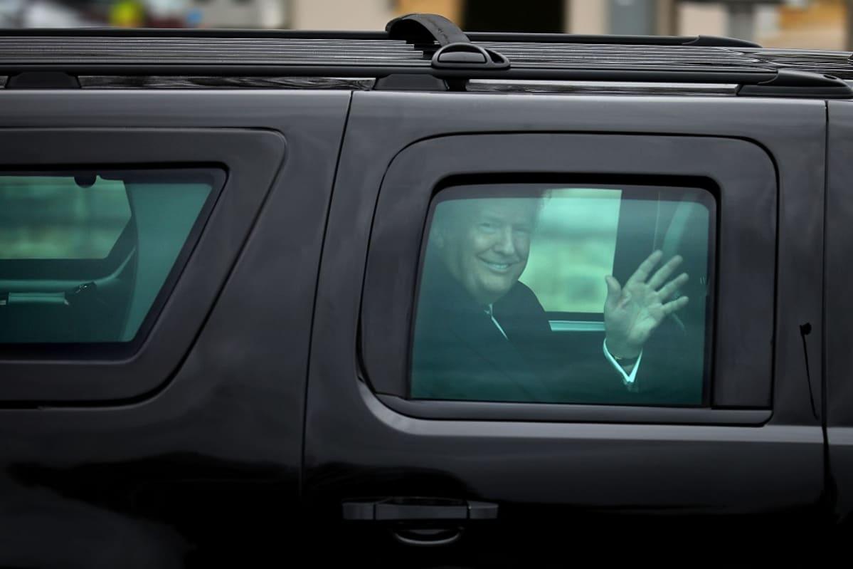 Trump vilkuttaa massiivisen mustan auton ikkunasta hymyillen leveästi.
