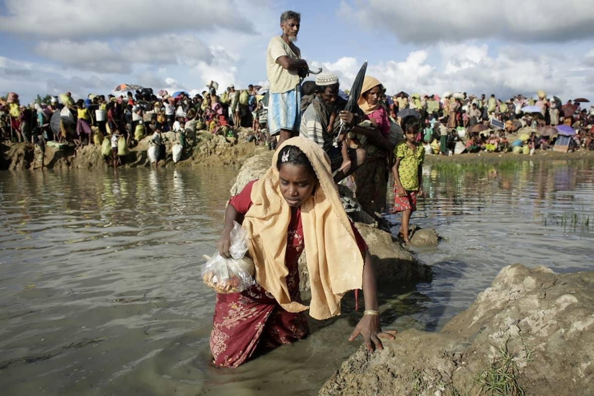 Nainen kulkee vedessä muovipussi kädessään. Taustalla näkyy suuri väkijoukko.