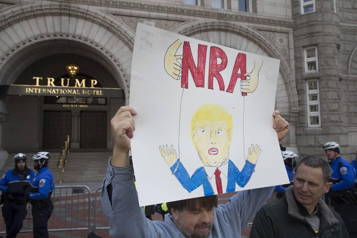Kuvassa mielenosoittaja kannattelee kylttiä, jossa on Donald Trumpin kuva ja teksti NRA. Viesti on, että NRA kontrolloi Trumpia.