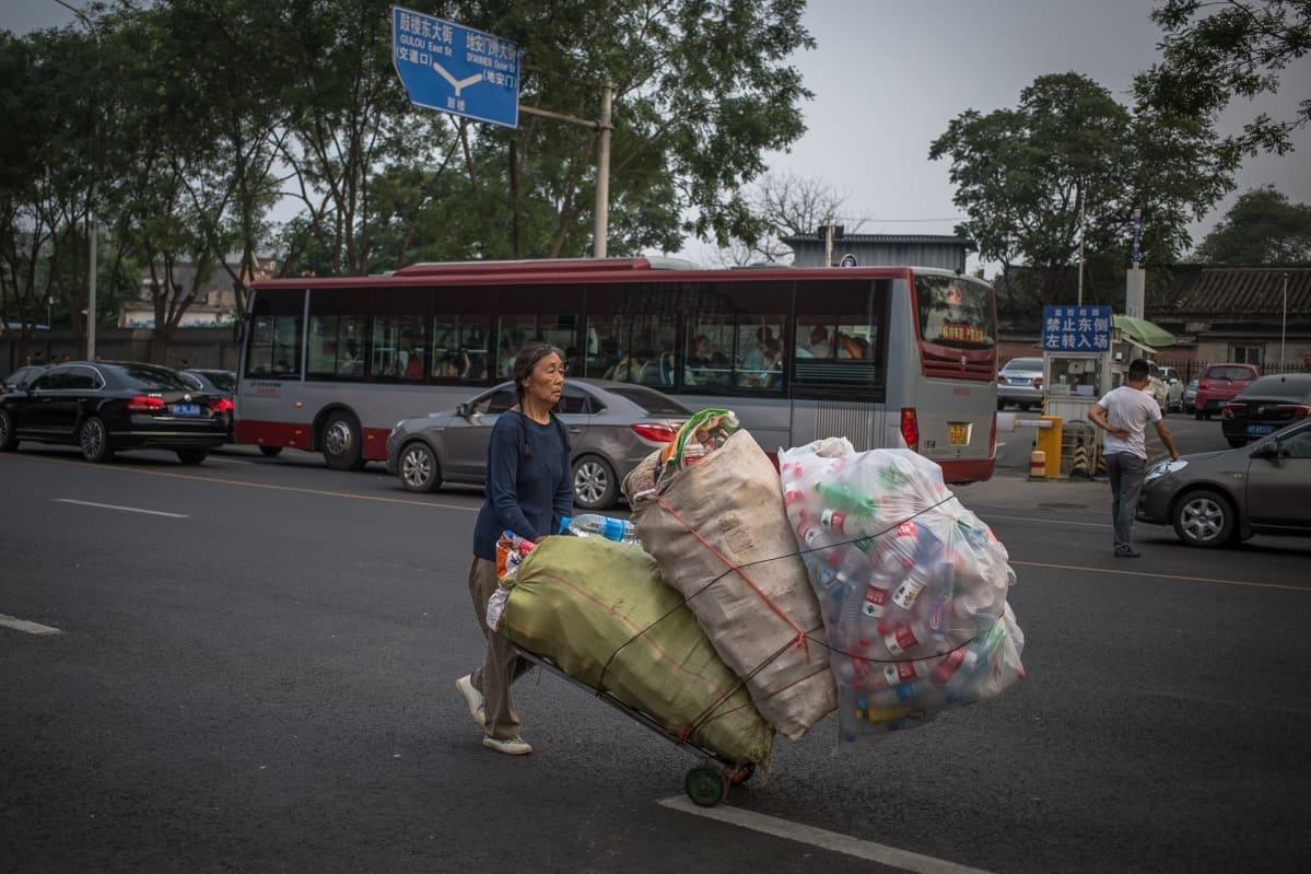 Nainen kerää muovipulloja Pekingissä.