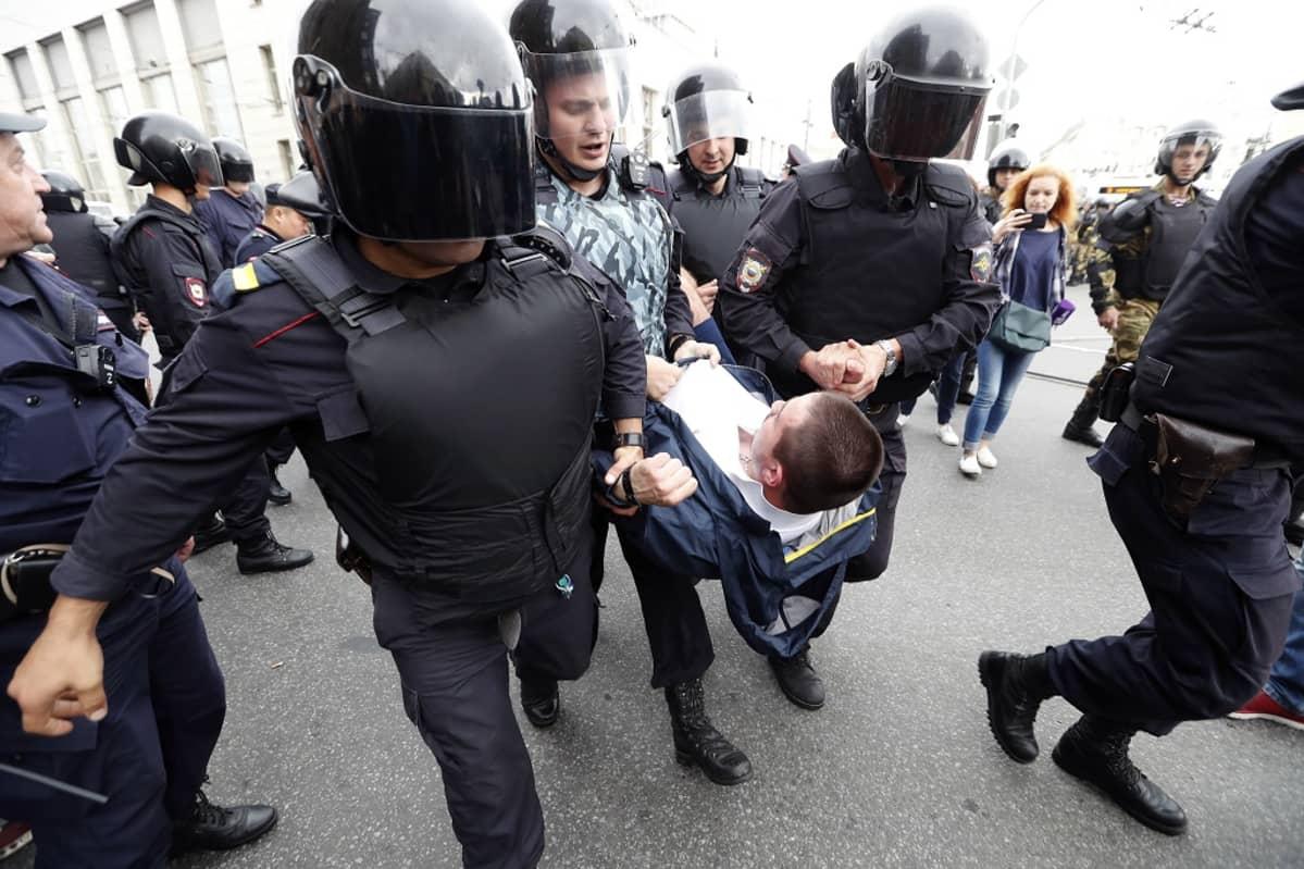 Neljä kypäräpäistä poliisia kantaa nuorta miestä. Taustalla näkyy lisää mielenosoittajia ja poliiseja.