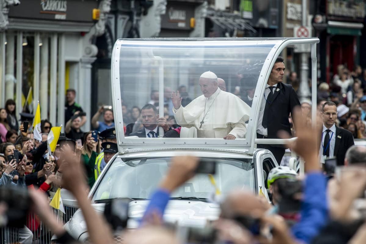 Paavi huiskuttaa paavimobiilista kadun laitoihin kerääntyneille ihmisille.